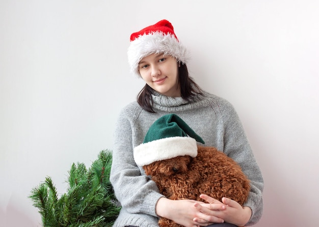 A teenage girl in a santa hat holds a miniature poodle in her arms.