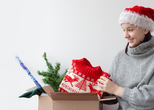 A teenage girl in a santa hat takes out a christmas sweater from a cardboard box