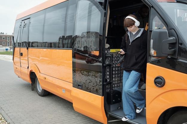 Девушка-подросток прокручивает в смартфоне, выходя из автобуса
