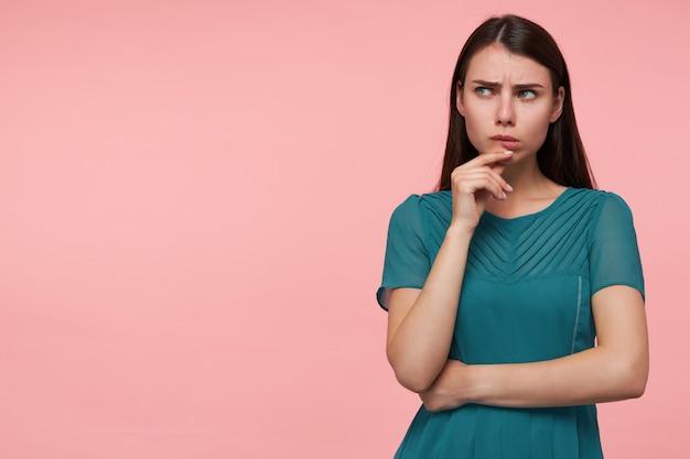10代の少女、ブルネットの長い髪の真面目な女性。手を胸に折り、あごに触れます。パステルピンクの壁の上のコピースペースで左を見てください。エメラルドドレスを着て