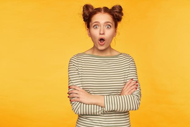 10代の少女、2つのパンを持つショックを受けた赤毛の女性。縞模様のセーターを着て、胸と驚きの顔に手を組んで見ています。黄色い壁の上に隔離されたスタンド