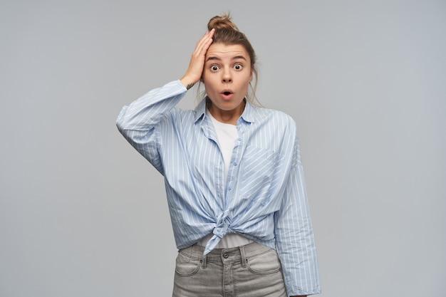 10代の少女、金髪のショックを受けた女性がお団子に集まった。縞模様の結び目のシャツを着ています。彼女の頭に触れる。ストーブの電源を切るのを忘れてください。灰色の壁に隔離されたカメラを見る