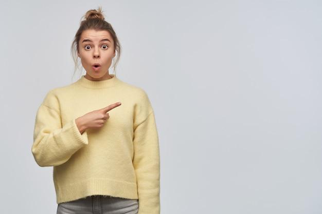 십 대 소녀, 금발 머리를 가진 충격 된 여자 롤빵에 모였다. 노란색 스웨터를 입고. 복사 공간에서 오른쪽을 손가락으로 가리 킵니다. 흰 벽에 고립 된 카메라를 보면