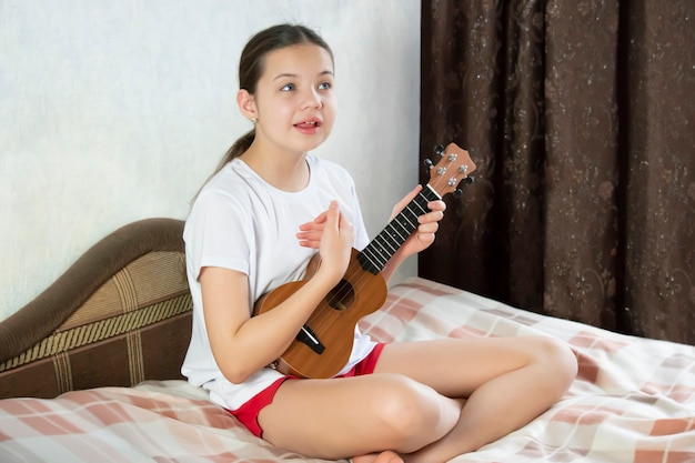 10代の少女はベッドに座って、ウクレレを演奏し、歌います