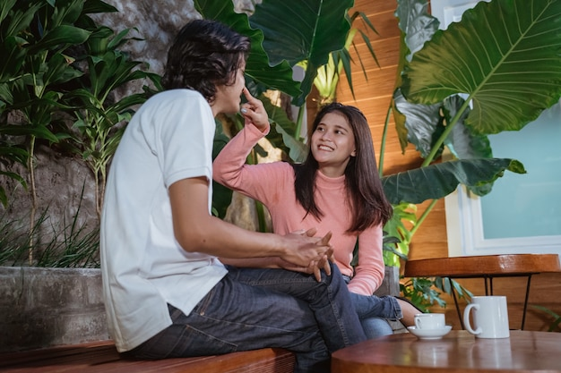 Teenage girl sits when joking and chatting with boyfriend in the garden
