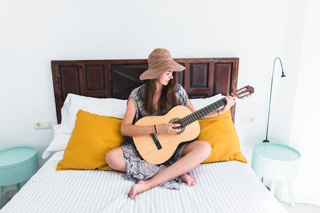 Teenage girl sitting on bed playing guitar