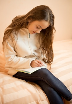 Teenage girl sitting on bed and writing in her notebook