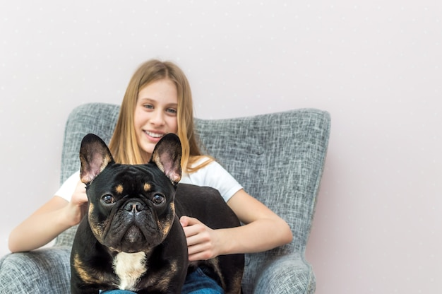 Teenage girl sitting in a chair at home with her french bulldog dog in her arms