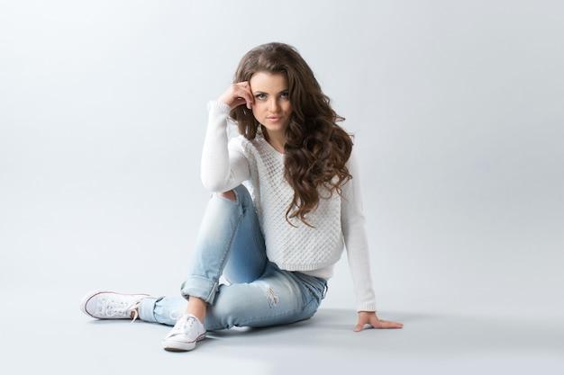 Девушка сидит. девушка с длинными волнистыми волосами.