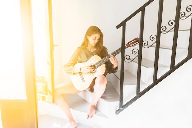 Teenage girl sitting near open door playing guitar