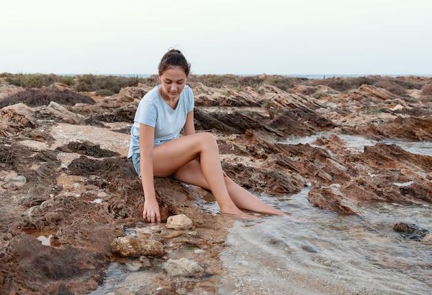 Девочка-подросток сидит на скале у моря