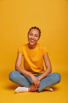 Девочка-подросток широко улыбается, оптимистично и расслабленно сидит на полу, носит повседневную одежду, чувствует себя позитивно, любит свободное время, скрещивает ноги, изолированные на желтой стене, веселится дома. эмоции, образ жизни