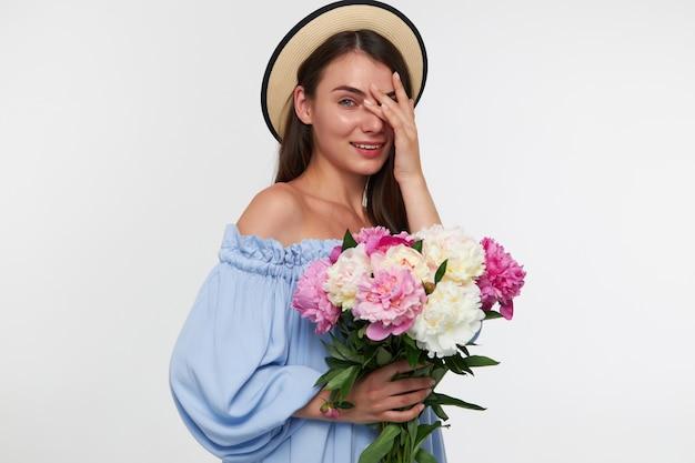 笑顔の10代の少女、ブルネットの長い髪の女性。帽子と青いかわいいドレスを着ています。花の花束を持って、白い壁に隔離された指を通して見ます