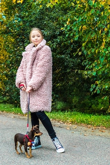Teenage girl in sneakers on a walk with the dog