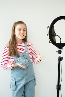 Teenage girl social media blogger recording video speaking looking at smartphone on tripod with ring light.