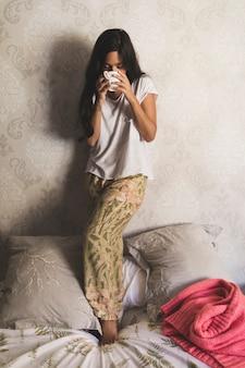 Teenage girl standing on bed drinking coffee