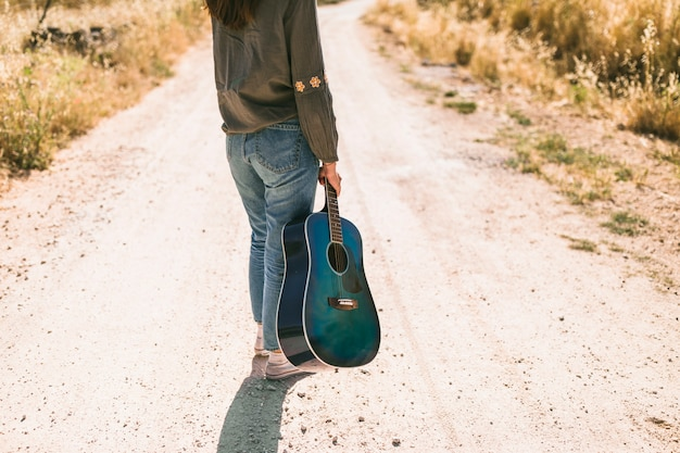 Teenage girl standing on dirt road holding guitar