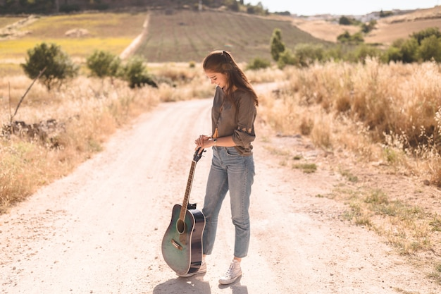 Teenage girl standing on dirt road with guitar at outdoors