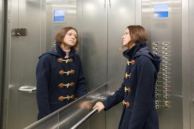 Teenage girl standing in elevator, looking in the mirror