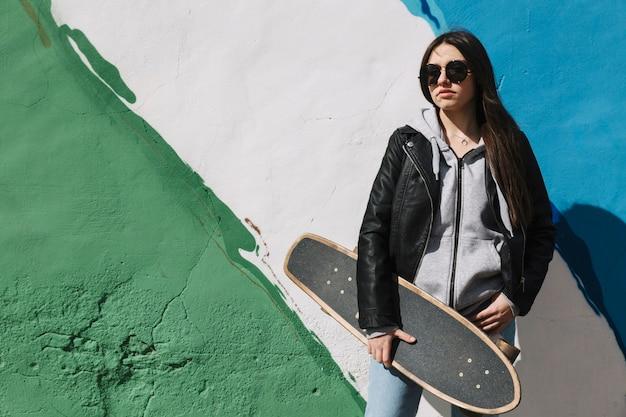 스케이트 보드를 손에 들고 컬러 벽 앞에 서있는 십 대 소녀
