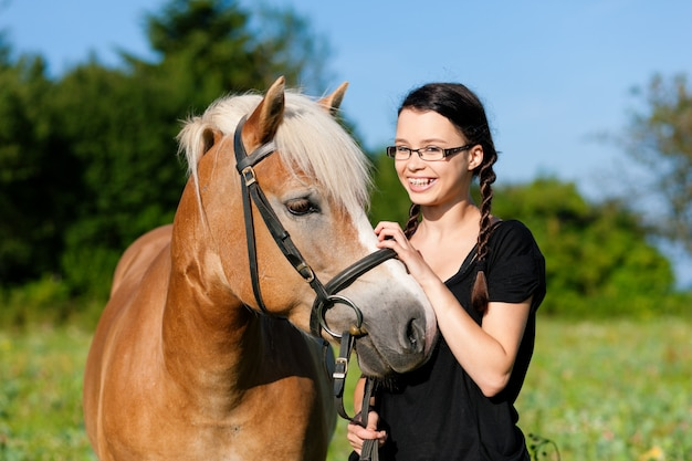 Teenage girl standing on a meadow in summer with her horse