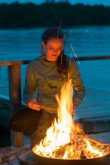 Teenage girl standing near campfire on dock, lake of the woods, ontario, canada