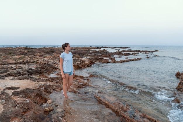 Девушка-подросток стоит на скале у моря на закате в голубой футболке, джинсовых шортах и смотрит в сторону. макет футболки