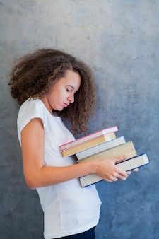 Teenage girl stands by the wall and holds several books