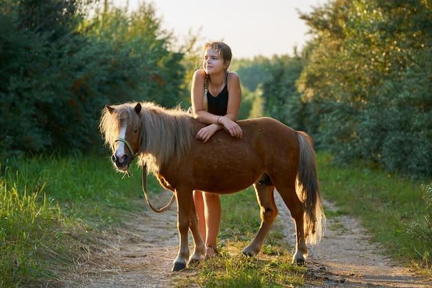 10代の少女が田舎道で小さな馬の背にもたれて立っています。