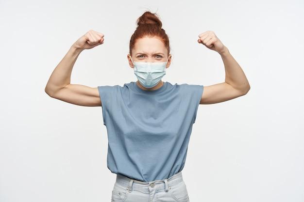 Ragazza adolescente, donna forte con i capelli rossi raccolti in una crocchia. indossare una maschera protettiva. stringi e alza i pugni. mostrando forza. isolato su muro bianco