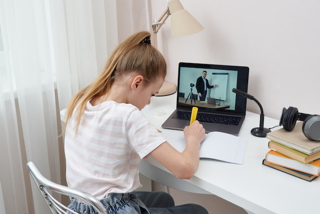 Teenage girl studying via video conference, e-learning with teacher and classmates on computer at home. homeschooling and distance learning ,online education concept, view through a door