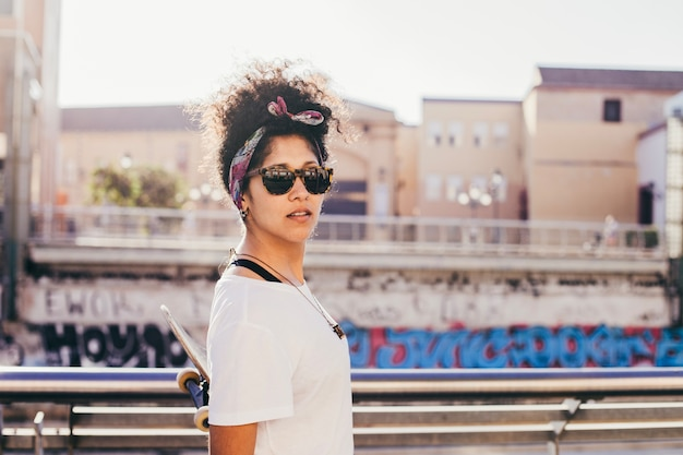 Teenage girl in sunglasses standing outside