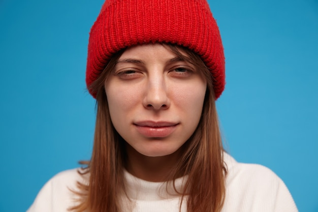 십 대 소녀, 의심스러운 갈색 머리를 가진 여자를 찾고. 흰색 스웨터와 빨간 모자를 쓰고. 사람과 감정적 인 개념. 근접 촬영, 파란색 벽 위에 절연