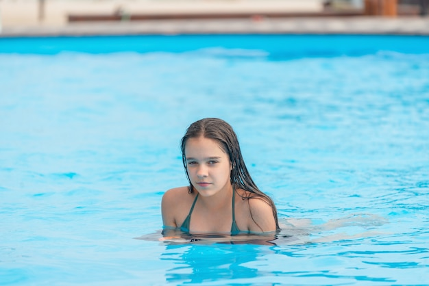 Teenage girl swims in the clear blue water of a pool during a vacation in a warm tropical country on a sunny warm summer day