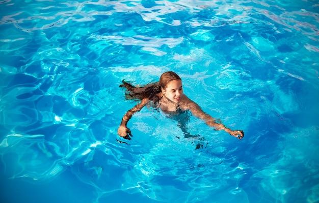10대 소녀는 화창한 여름날 따뜻한 열대 나라에서 휴가를 보내는 동안 수영장의 맑고 푸른 물에서 수영합니다. 여행 개념입니다. 광고 공간
