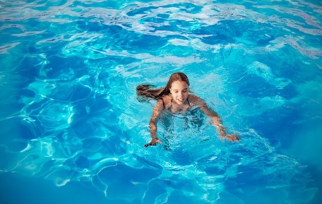 십 대 소녀는 화창한 따뜻한 여름 날에 따뜻한 열대 국가에서 휴가 기간 동안 수영장의 맑고 푸른 물에서 수영합니다. 여행 개념.
