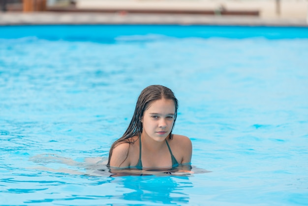10代の少女は、暖かい熱帯の国での休暇中にプールの澄んだ青い水で泳ぐ