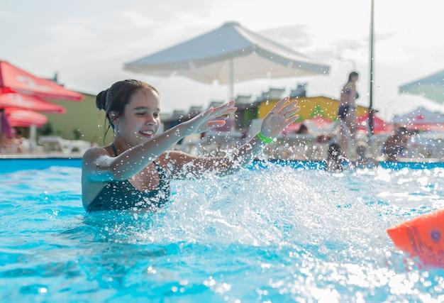 십대 소녀는 따뜻한 열대 국가에서 휴가 기간 동안 수영장의 맑고 푸른 물에서 수영