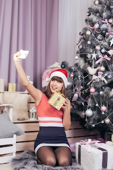 Teenage girl takes a selfie with a golden christmas present amid festive new year's decorations of pink color.