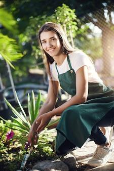 Девочка-подросток заботится о цветах, работая продавцом в магазине теплицы, глядя на камеру улыбается.