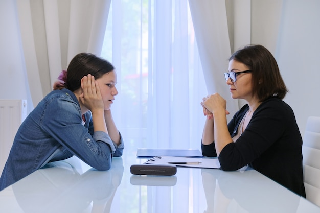 Teenage girl talking with counselor psychologist about her feelings