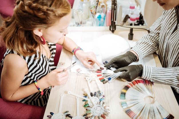 Teenage girl. teenage girl wearing striped dress and bracelets showing color of shellac she wants