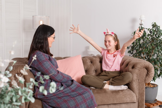 Teenage girl tells a story emotionally waving her arms to her psychologist