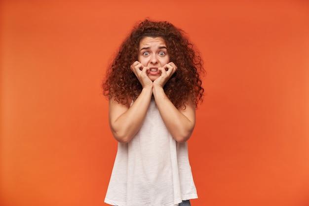 Ragazza adolescente, donna dall'aspetto terrificante con i capelli ricci di zenzero. indossare camicetta bianca con spalle scoperte. toccandole il viso. ha la paura sul viso. isolato sopra il muro arancione