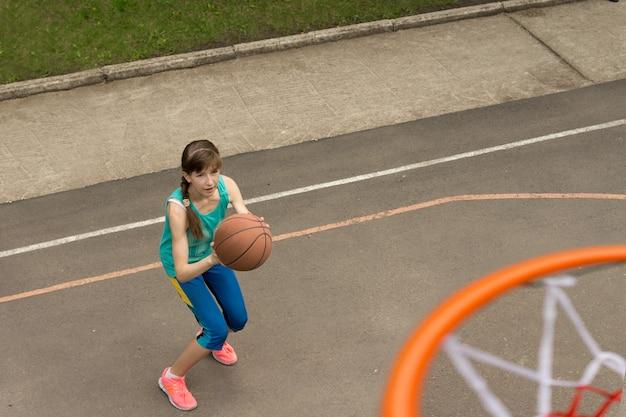 バスケットボールを投げる10代の少女