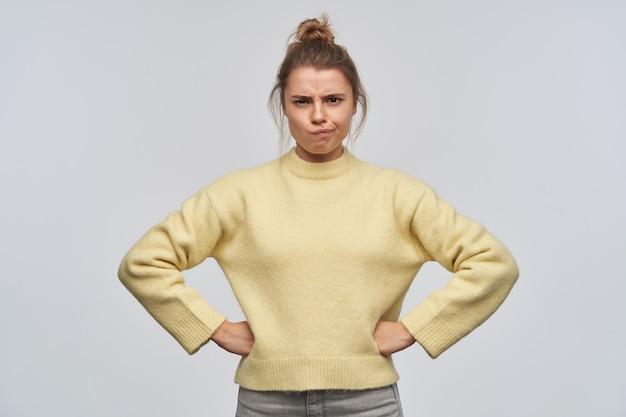 Ragazza adolescente, donna dall'aspetto infelice con i capelli biondi raccolti in un panino. indossare un maglione giallo. aggrotta le sopracciglia e si mette le mani sui fianchi. guardando la telecamera, isolata sul muro bianco