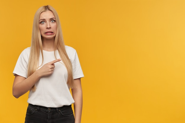 Teenage girl, unhappy looking woman with blond long hair. wearing white t-shirt and black jeans. people and emotion concept. pointing to the right at copy space with a disgust facial expression