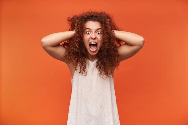 10代の少女、巻き毛の生姜髪の不幸な女性。白いオフショルダーのブラウスを着ています。彼女の頭に触れて悲鳴を上げ、ぞっとした。オレンジ色の壁に隔離