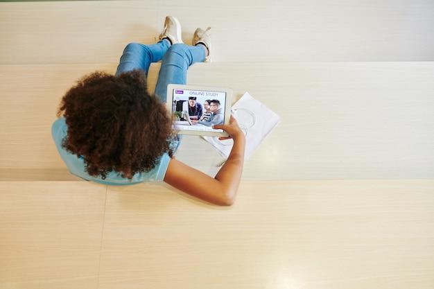Девушка-подросток использует приложение на планшетном компьютере для учебы из дома из-за вспышки коронавируса