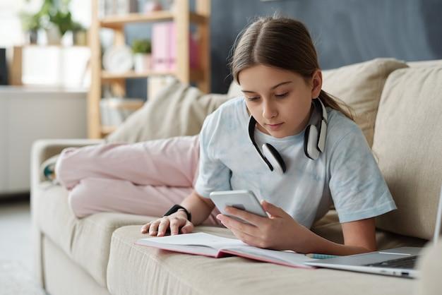 開いた本とラップトップの前でソファに横になり、自己隔離中にリモートで勉強しながらスマートフォンを使用して10代の少女